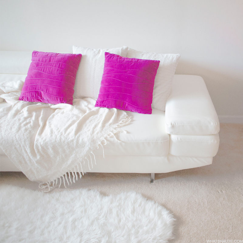 Home: White leather couch with purple pillows